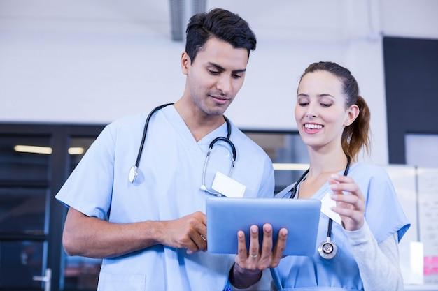 Artsen die digitale tablet gebruiken en in het ziekenhuis glimlachen