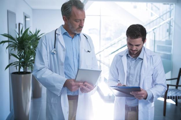 Artsen die digitale tablet gebruiken terwijl het schrijven op klembord in gang
