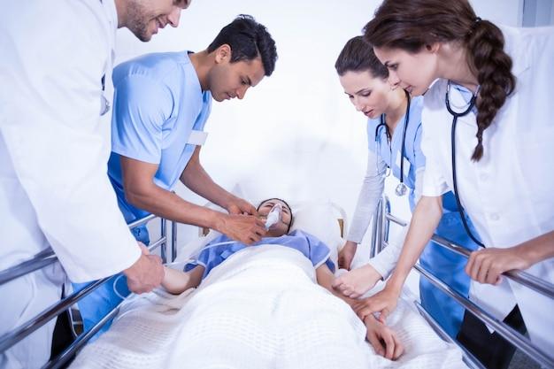 Artsen die een patiënt op bed in het ziekenhuis onderzoeken