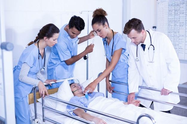 Artsen die een zuurstofmasker op patiënt zetten en iv druppel in het ziekenhuis aanpassen