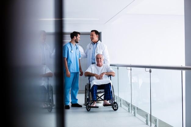 Artsen die elkaar met patiënt op rolstoel in gang in wisselwerking staan