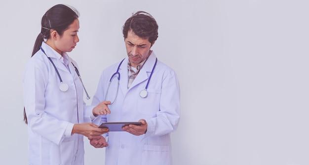Artsen die geduldige informatie controleren op een tabletapparaat, conceptengroepswerk