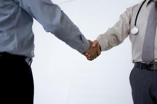 Artsen die handen schudden aan elkaar die medische vergadering beëindigen die op grijze achtergrond wordt geïsoleerd.