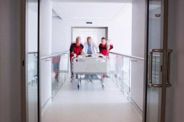 Artsen die het bed van de noodsituatiebrancard in gang duwen