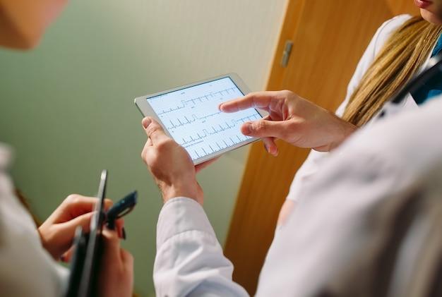 Artsen die het cardiogram van de patiënt op de tablet bespreken.