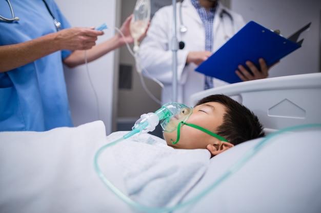 Artsen die iv druppel aanpassen terwijl patiënt die op bed ligt