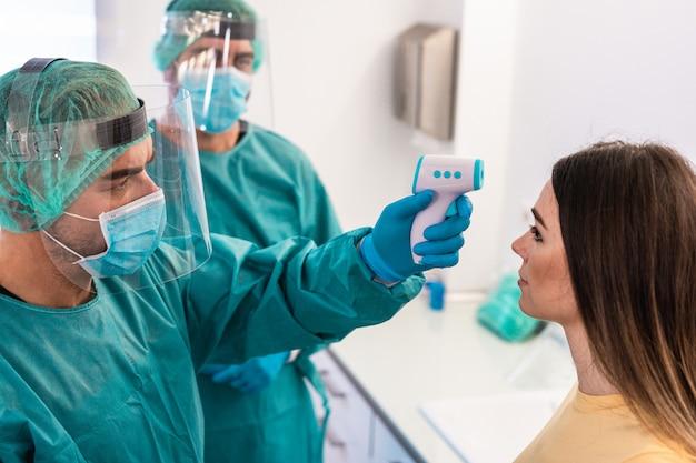 Artsen die koorts meten aan een jonge patiënt