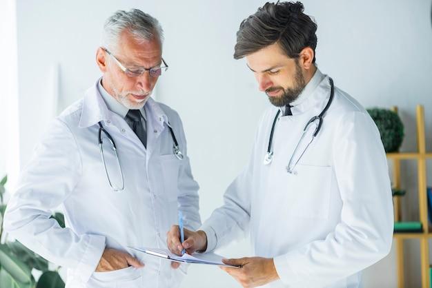Artsen die met documenten in bureau werken