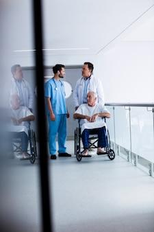 Artsen die met elkaar in wisselwerking staan met patiënt op rolstoel in gang