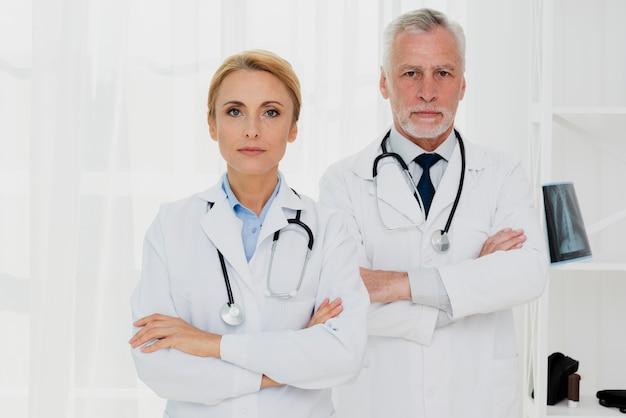 Artsen die met gekruiste handen camera bekijken