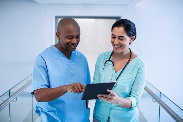 Artsen die over digitale tablet in gang bespreken