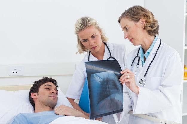 Artsen die radiografie tonen aan een patiënt