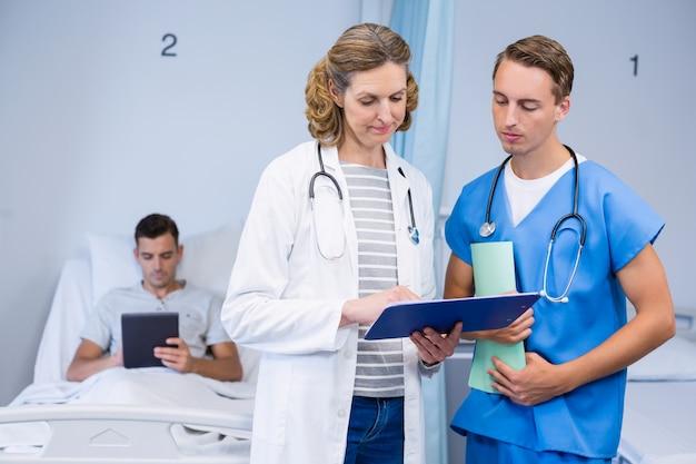 Artsen die rapporten onderzoeken en patiënt die digitale tablet gebruiken