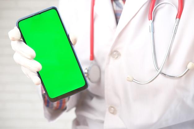 Artsen dienen beschermende handschoenen in met slimme telefoon met groen scherm