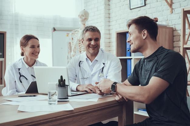 Artsen en atleet praten in de kamer
