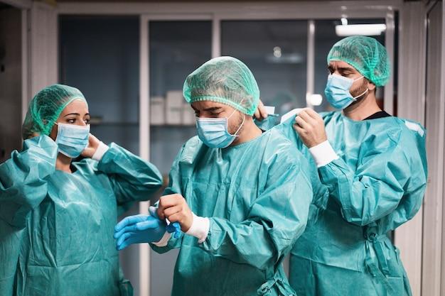 Artsen en verpleegster bereiden zich voor om in het ziekenhuis te werken voor een chirurgische ingreep tijdens coronavirus-pandemie