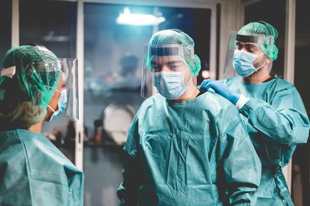 Artsen en verpleegster bereiden zich voor om in het ziekenhuis te werken voor een chirurgische ingreep tijdens de uitbraak van een coronavirus-pandemie