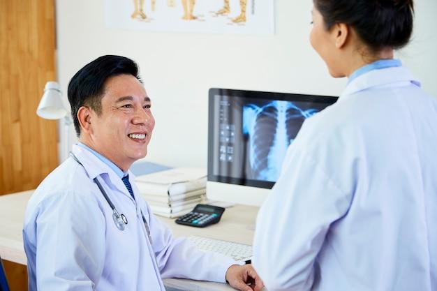 Artsen en verpleegster werken op kantoor