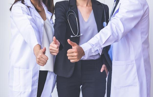 Artsen en verpleegsters coördineren hands.doctors duim omhoog, concept teamwork
