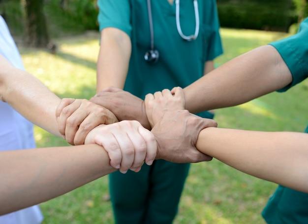 Artsen en verpleegsters in een medisch team die handen openlucht stapelen op de groene parkachtergrond (vrijwilliger)