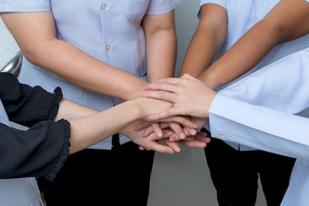 Artsen en verpleegsters in een medisch team stapelen handen