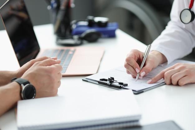 Artsen handen patiënten klachten in medische geschiedenis close-up opschrijven. medisch consult concept