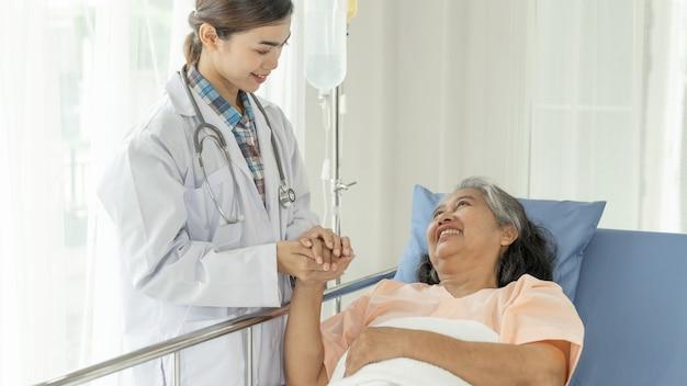 Artsen houden handen vast om oudere oudere vrouwenpatiënten in het ziekenhuis-senior vrouwelijke medische en gezondheidszorgconcept aan te moedigen