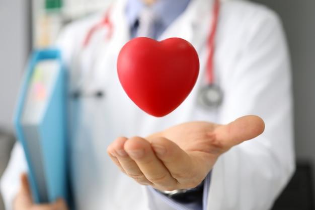 Artsen houden in hand rood stuk speelgoed hert tegen het ziekenhuis