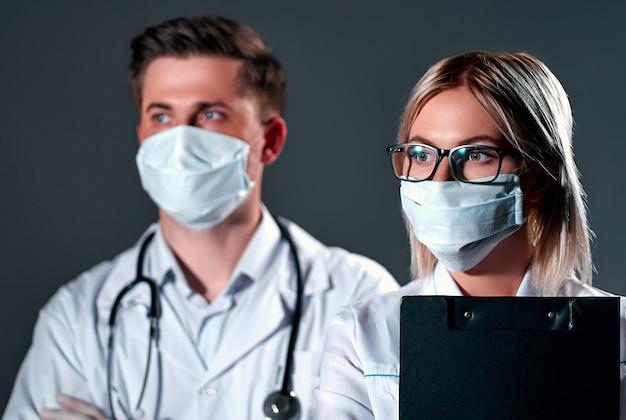 Artsen in beschermende maskers en handschoenen op een donkergrijze achtergrond