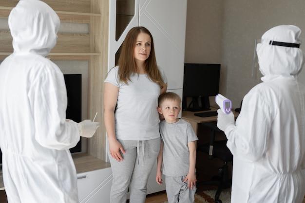 Artsen in beschermende pakken bij zieke patiënten thuis coronavirus