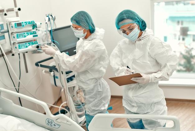 Artsen in beschermende pakken en maskers houden de toestand van de patiënt in de gaten