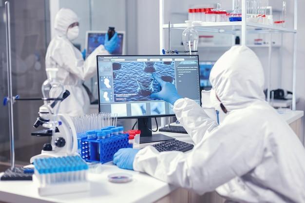 Artsen in de gezondheidszorg die de evolutie van het coronavirus onderzoeken terwijl ze op een computer werken, gekleed in een overall