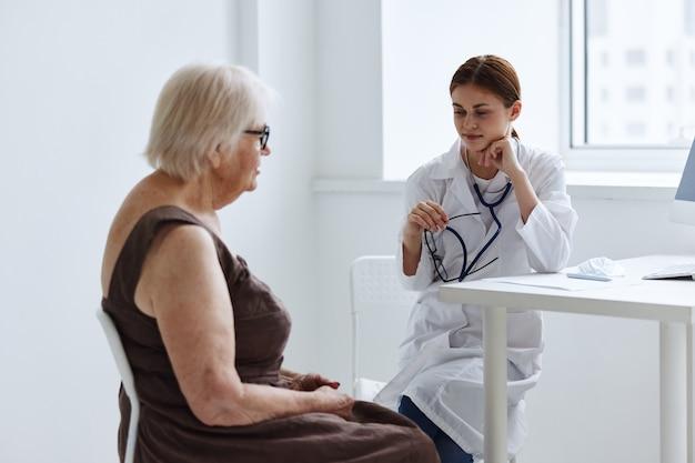 Artsen in het medische kantoor praten met een oudere vrouw gezondheidsdiagnostiek