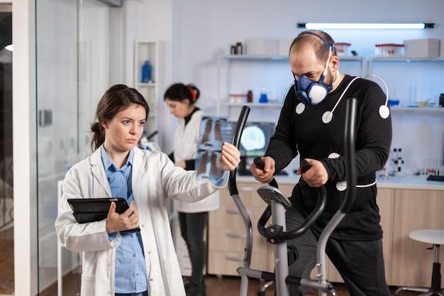Artsen in het sportwetenschappelijk laboratorium die de cardiorespiratoire prestaties van de atleet meten. team van onderzoeker die vo2 bewaakt van sportman die op crosstrainer loopt die is uitgerust met elektroden en masker.
