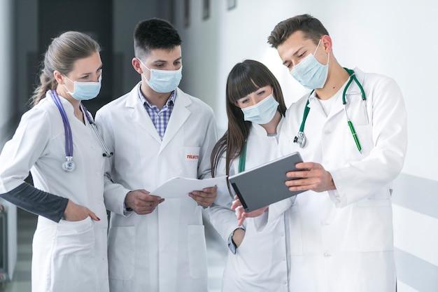 Artsen in maskers die tablet gebruiken