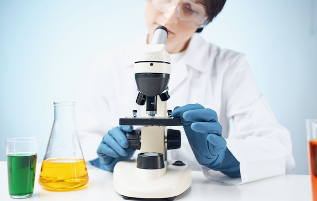 Artsen in medische handschoenen kijken door een microscoop op het scheikundig element table e laboratorium
