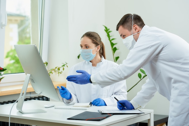 Artsen in medische maskers bespreken röntgenfoto's van een patiënt