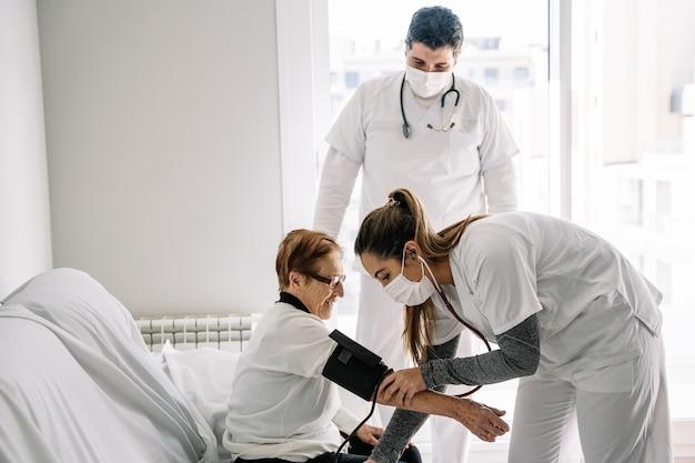 Artsen in medische maskers met behulp van tonometer en het meten van de bloeddruk van oudere vrouwelijke patiënt zittend op de bank thuis