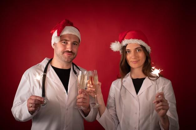 Artsen in santa claus-hoeden juichen met champagneglazen en wonderkaarsen te houden