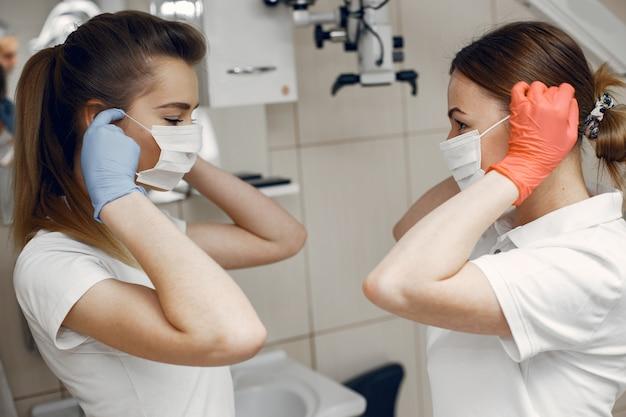 Artsen in speciaal uniform tandartsen dragen beschermende maskers. meisjes kijken elkaar aan