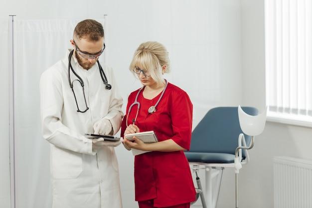 Artsen in uniform, man en vrouw in een gynaecologisch kantoor.