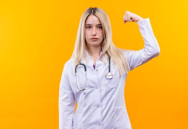 Artsen jong meisje dat stethoscoop in medische toga draagt die sterk gebaar op geïsoleerde gele muur doet