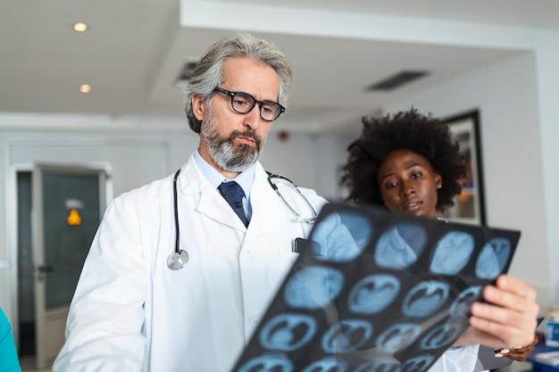 Artsen kijken naar longen röntgenstraal in het ziekenhuis tijdens covid19 pandemie