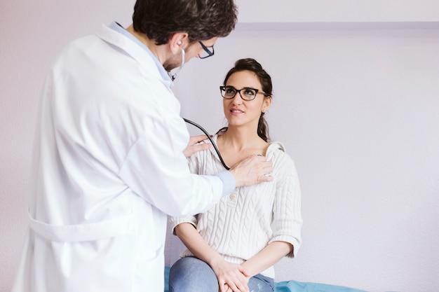 Artsen mannelijk auscultating geduldig wijfje met stethoscoop. arts raadplegen. medisch concept