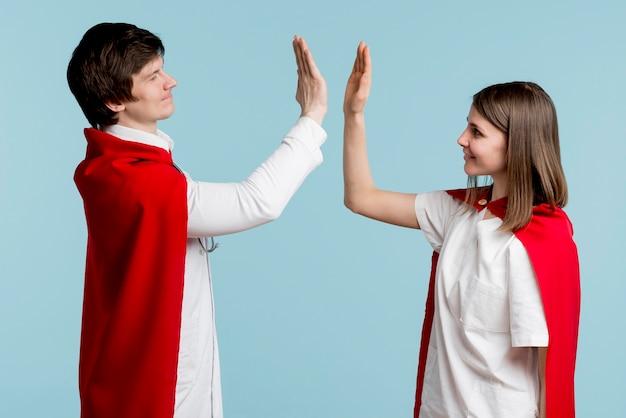 Artsen met capes high fiving