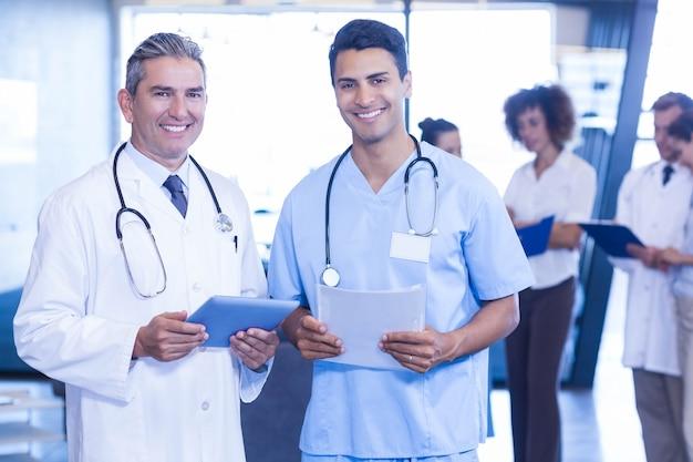 Artsen met digitale tablet en medisch rapport die en in het ziekenhuis kijken glimlachen