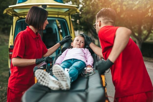Artsen met gewond meisje voor ambulance auto.