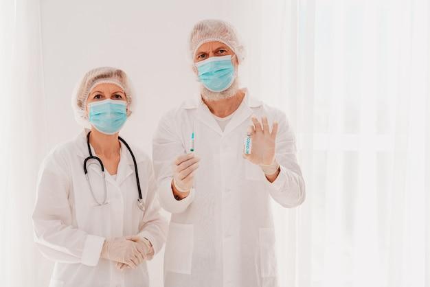 Artsen met gezichtsmasker staan klaar om met het vaccin tegen het covid-virus aan de slag te gaan Premium Foto
