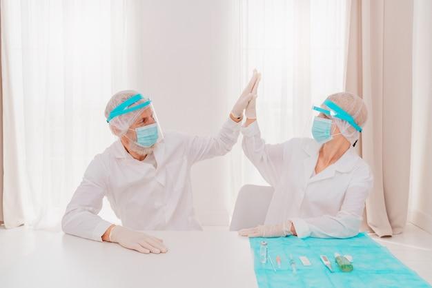 Artsen met masker en gezichtsbeschermer staan klaar om in het ziekenhuis aan de slag te gaan