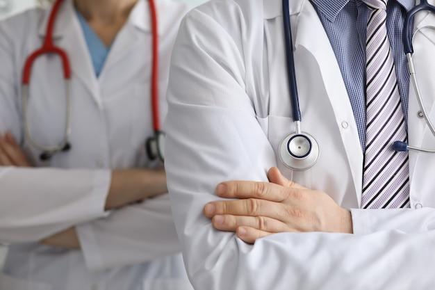 Artsen met stethoscopen om hun nek staan met gekruiste armen close-up